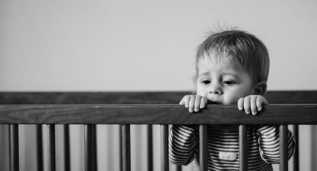 Ill toddler holding onto crib.