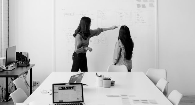 Women working at a whiteboard in a boardroom.