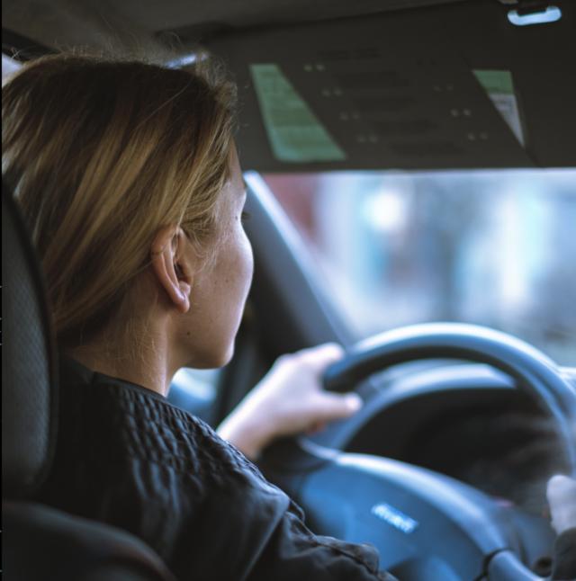 Woman behind steering wheel.