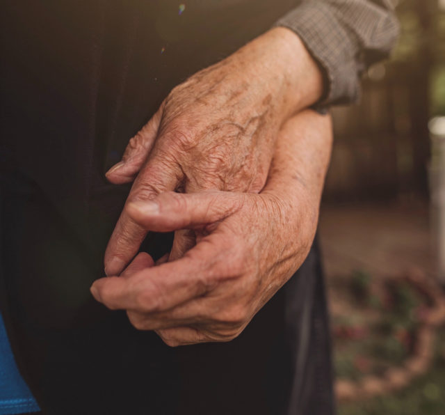 Two elderly hands holding each other.