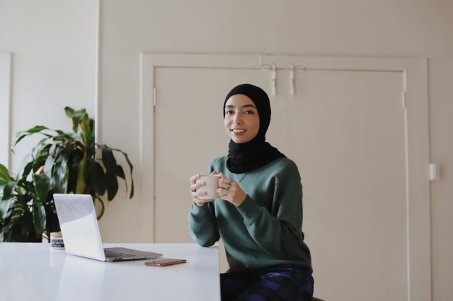 Female smiling with coffee cup at work station.