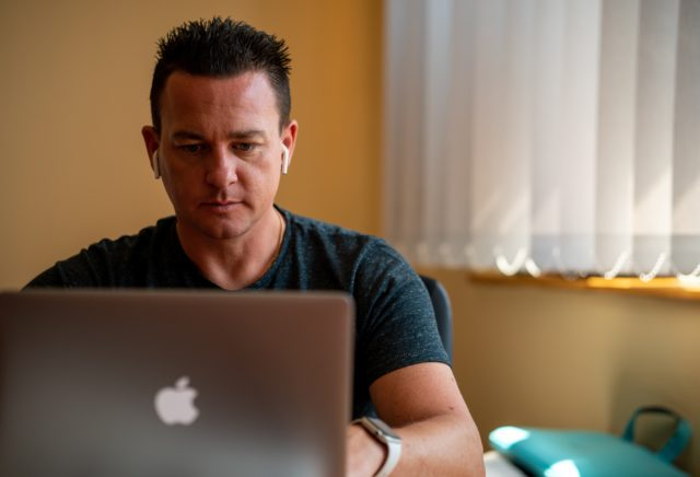 Male working at laptop with headphones in.